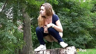Chick pulls down her jeans and pees on a stump