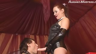 Leather babe makes the slave suck her strapon and bend over for it