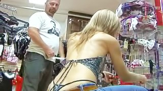 Provocative slender pale mature blonde cougar with natural boobs and sexy tight ass in thong and jeans has fun with tuned on worker in sexy shop on a lazy afternoon